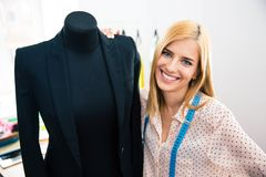Female tailor standing holding mannequin Royalty Free Stock Photo
