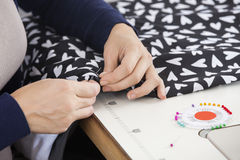 Female Tailor Stitching Fabric At Workbench. Cropped image of female tailor stitching fabric at workbench in sewing factory Royalty Free Stock Image