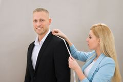Female Tailor Taking Measurement Of Suit Stock Images