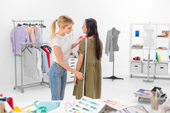 Female tailor taking measurments. Young dressmaker gets hight measures of client in the showroom Stock Image