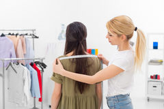 Female tailor taking measurments. Young dressmaker gets shoulders measures of client in the showroom Royalty Free Stock Image