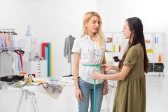 Female tailor taking measurments. Young dressmaker gets waist measures of client in the showroom Royalty Free Stock Photos