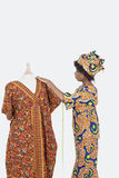 Female tailor in traditional outfit measuring dashiki on tailor's dummy over gray background Stock Photos
