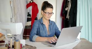 Female tailor using laptop at work stock footage