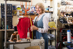 Female tailor working near mannequin in sewing workshop Royalty Free Stock Image