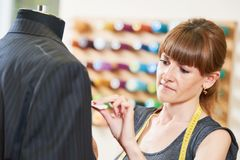 Female tailor works with male suit. Young female tailor works with male suit in workshop Royalty Free Stock Photos