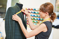Female tailor works with male suit. Young female tailor works with male suit in workshop Stock Image