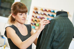 Female tailor works with male suit. Young female tailor works with male suit in workshop Stock Photography