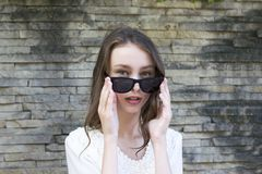 Cute girl posing in sunglasses stock photography