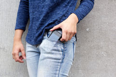 Female taking out mobile phone from her pants Stock Photo