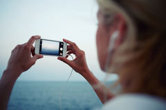 Female taking photo of ocean view with mobile phone camera and listening to music in headphones Stock Images