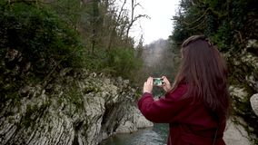 Female taking photos at Canyon Devil`s Gate in Sochi, Russia. stock footage