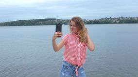 Female taking photos on her phone near lake in slow motion stock video footage