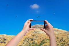 Female taking picture of landscape of mountain birds and sky on smart phone. Birds eagle flying above mountain in mobile phone. Da. Female taking picture of Stock Photography