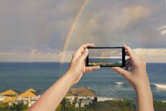 Female taking picture on mobile phone of double rainbow over ocean and tropical beach with umbrellas chairs and tables Stock Image