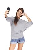 Female taking pictures of herself at smart phone Royalty Free Stock Images