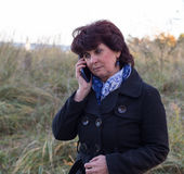 Female talking on her cell. Beautiful mature female is talking on the phone Stock Photography