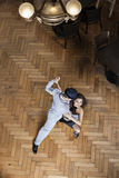 Female Tango Dancer Performing With Man On Hardwood Floor. High angle portrait of female tango dancer performing with men on hardwood floor at restaurant Royalty Free Stock Photos