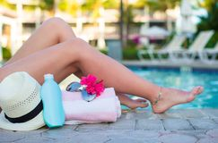 Female tanned legs near sun cream, hat, towel and sunglasses against the swimming pool Royalty Free Stock Photo