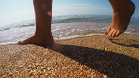 Female tanned legs walking along the sea shore leaving marks on the sand. The average plan stock footage