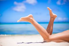 Female tanned slim legs on the white sandy Royalty Free Stock Photo