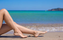 Female tanned slim legs on the white sandy Stock Image