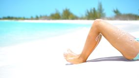 Female slim tanned legs on a white tropical beach. Slow video. Female tanned slim legs on the white sandy tropical beach stock video