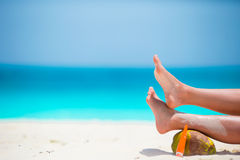 Female tanned smooth legs with suncream and coconut on white beach Stock Photo