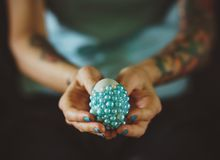 Female tattoos hands hold decorated Easter egg. The concept of turquoise color stock photos