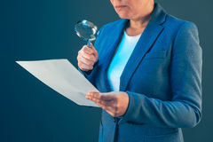 Female tax inspector looking at document with magnifying glass Stock Image