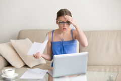 Female taxpayer forgot to submit tax return. Worried young woman in eyeglasses sitting on sofa with paper letter in hand and looking with confusion on laptop Royalty Free Stock Photography