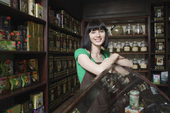 Female Tea Shop Owner Leaning On Display Cabinet. Portrait of confident female tea shop owner leaning on display cabinet stock photos