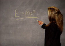 Female teacher. Writing formula on a blackboard stock photography