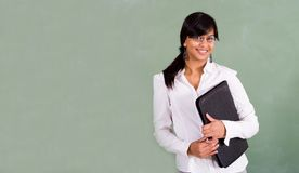 Female teacher. Portrait of a female young beautiful indian school teacher in front of blackboard royalty free stock photography