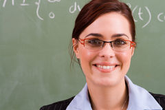 Female teacher. Beautiful cheerful female teacher in classroom stock image