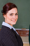 Female teacher. Beautiful female school teacher in school classroom stock photo