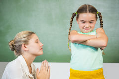 Female teacher apologizing girl in the classroom. At school Royalty Free Stock Images
