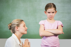 Female teacher apologizing girl in the classroom. At school stock photo