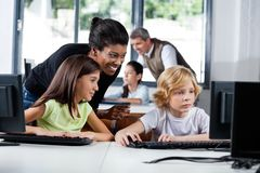Female Teacher Assisting Schoolchildren In Using. Happy female teacher assisting schoolchildren in using computer at school Royalty Free Stock Photos