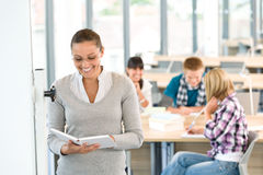 Female teacher with book and students in classroom Royalty Free Stock Photo