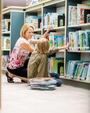 Female Teacher And Boy Selecting Books In Library Royalty Free Stock Photos
