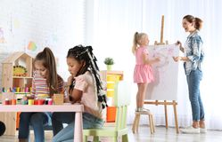 Female teacher with child near easel at painting lesson. Indoors royalty free stock photography