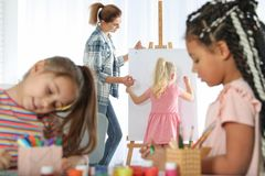 Female teacher with child near easel at painting lesson. Indoors stock images