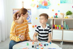 Female teacher with child at painting lesson. Indoors royalty free stock photos