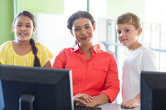 Female teacher with children in computer class. Portrait of smiling female teacher with children in computer class Royalty Free Stock Photos