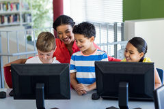 Female teacher with children during computer class. Smiling female teacher with children during computer class Stock Photo