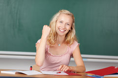 Female Teacher With Clenched Fist At Desk. Portrait of happy young female teacher with clenched fist at classroom desk Royalty Free Stock Photo