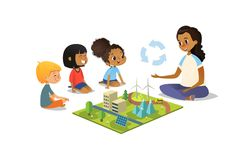 Female teacher discusses ecology Green-city using model landscape, children sit on floor in circle and listen to her. Preschool activities and early childhood Royalty Free Stock Photos