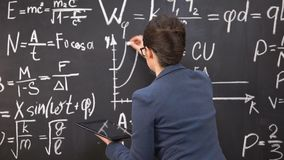 Female teacher drawing graph on chalkboard and holding tablet, innovations. Stock footage stock footage