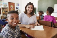 Female teacher and elementary school boy smiling to camera Stock Image